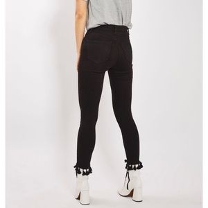 Black jeans with tasseled hem